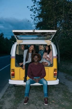 Photo pour Amis multiethniques voyageant ensemble en minifourgonnette rétro le soir - image libre de droit