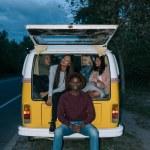 Friends traveling on retro minivan