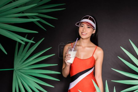Woman in swimsuit and visor drinking milkshake