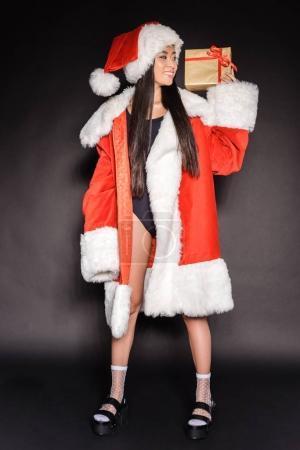 Photo pour Pleine longueur de souriante femme asiatique en maillot de bain noir et costume de Père Noël, avec un cadeau et regarder de côté - image libre de droit