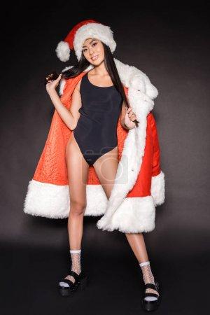 Photo pour Pleine longueur de sourire asiatique femme en noir maillot de bain et santa robe posant sur noir et regardant caméra - image libre de droit