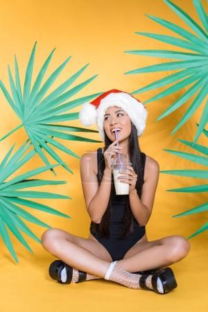 Photo pour Pleine longueur de sourire femme asiatique en maillot de bain noir et santa chapeau assis jambes croisées sur le sol, boire milkshake - image libre de droit