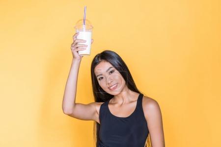 Photo pour Pleine longueur de sourire asiatique femme tenant jusqu 'un verre de milkshake sur jaune - image libre de droit