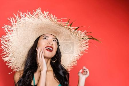Smiling woman in swimsuit and beach hat