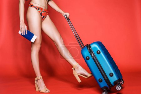 Woman in swimsuit walking with suitcase