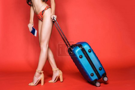 woman in swimsuit holding suitcase