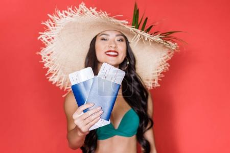 woman in swimsuit showing airplane tickets