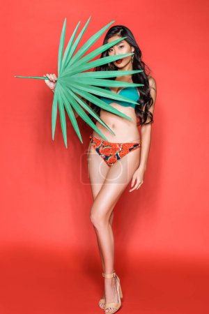 Woman covering face with palm leaf