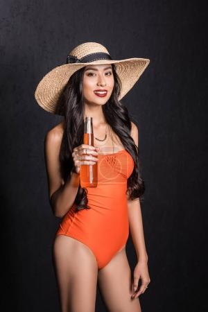 woman in swimsuit holding soda