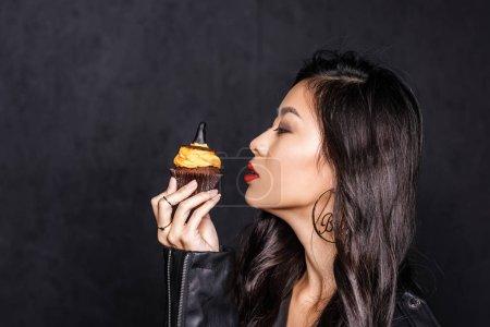 woman holding up halloween cupcake