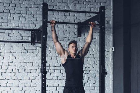 Photo pour Jeune homme Sportswear faisant tirer ups sur pull up bar dans la salle de gym - image libre de droit