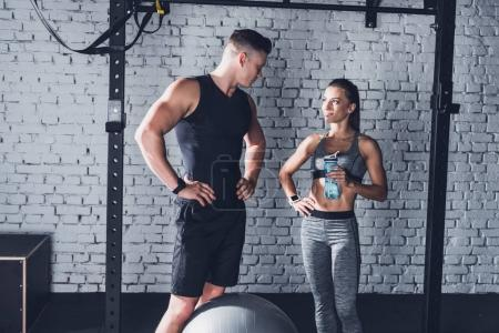 Photo for Smiling woman with sportive water bottle and athletic boyfriend looking at each other in gym - Royalty Free Image
