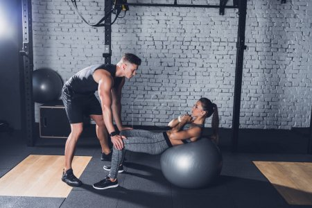 Photo for Side view of trainer holding sportive woman while she working out on fitness ball in gym - Royalty Free Image