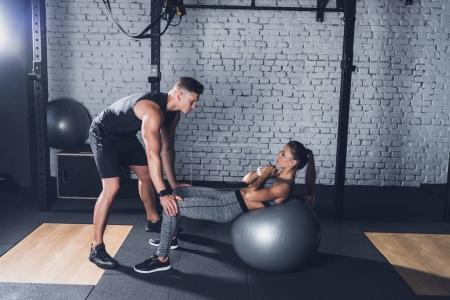 trainer helping woman work out