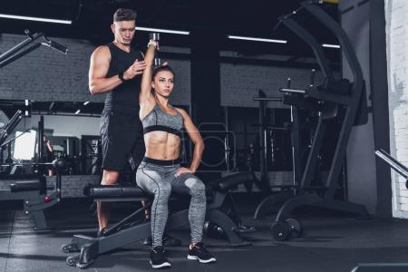 Photo for Young trainer helping athletic woman to exercise with dumbbell in gym - Royalty Free Image