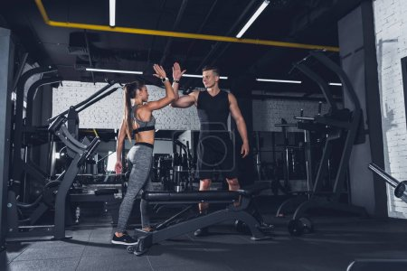 Photo for Sportive couple giving high five to each other in gym - Royalty Free Image