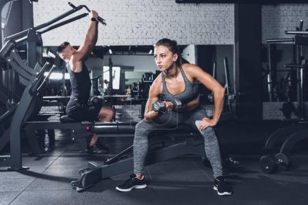 Photo for Selective focus of athletic man pumping muscles with barbell in hand in gym - Royalty Free Image