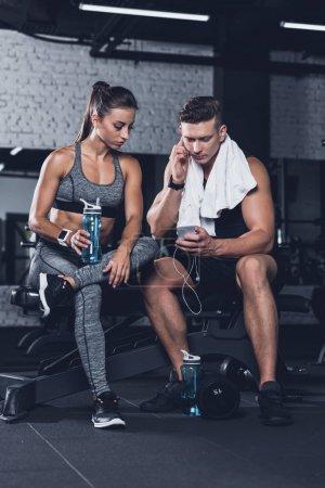Foto de Pareja deportiva utilizando el teléfono inteligente juntos mientras descansan después de entrenar en el gimnasio - Imagen libre de derechos