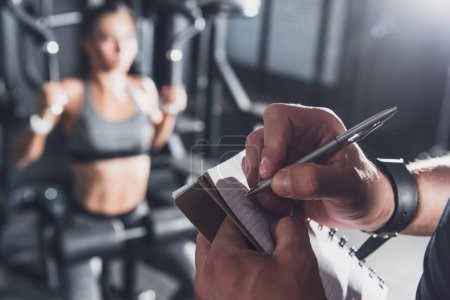 Photo for Close up view of trainer writing in notebook while woman working out in gym - Royalty Free Image