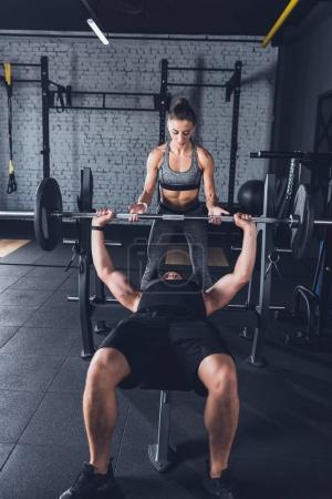 woman helping man to lift barbell