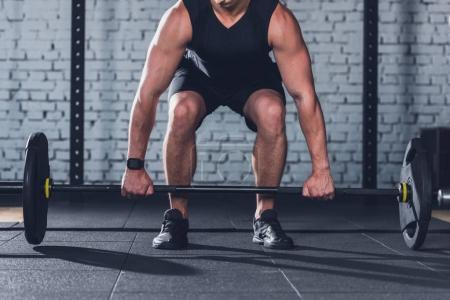 Photo for Partial view of man in sportswear lifting barbell in gym - Royalty Free Image