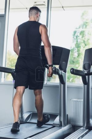 Photo for Back view of man in sportswear exercising on treadmill in gym - Royalty Free Image