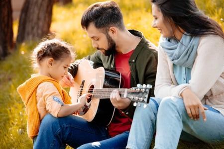 Photo pour Famille avec fille se détendre sur une colline herbeuse pendant que le père joue de la guitare - image libre de droit