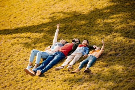 Family resting on grass