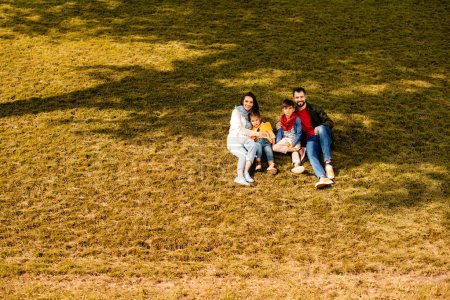 Family sitting on grassy hill