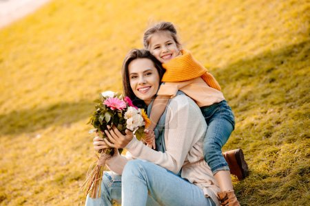 Photo for Happy woman holding bouquet of flowers while daughter hugging her - Royalty Free Image