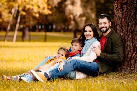 Happy family leaning on tree