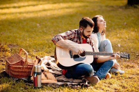 Photo pour Jeune homme assis sur la couverture de pique-nique avec sa petite amie et jouer de la guitare - image libre de droit