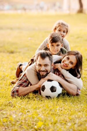 Family lying in pile on grass