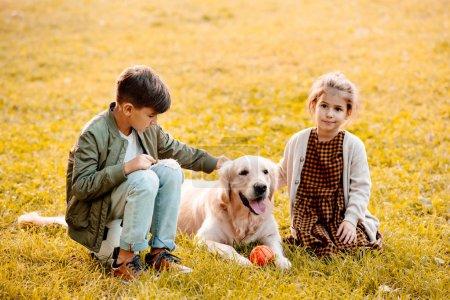 Children petting dog in park