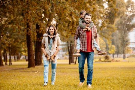 Photo pour Parents de donner à leurs enfants un piggyback ride dans un parc en automne - image libre de droit