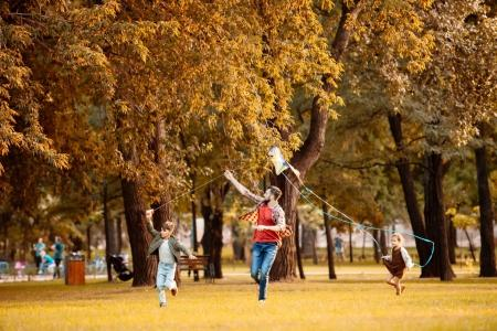 Photo for Father and two children running across the autumn park and flying a kite - Royalty Free Image