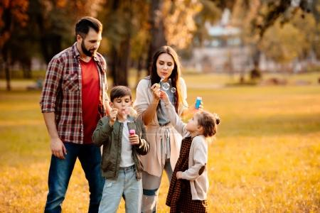 Family with children blowing bubbles