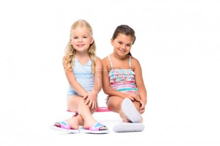 Photo for Adorable little girls sitting on skateboard and smiling at camera isolated on white - Royalty Free Image