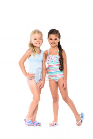 Photo for Adorable little girls in swimsuits smiling at camera isolated on white - Royalty Free Image