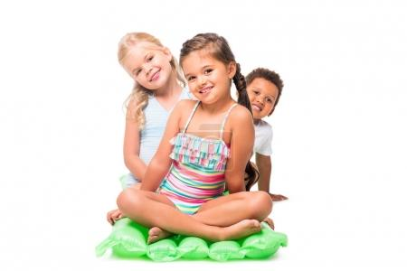 multiethnic kids on swimming mattress