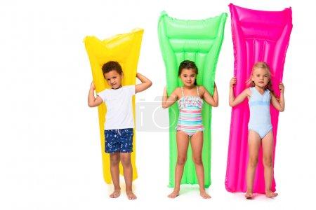 Photo pour Mignon multiethnique enfants tenant matelas de natation et regardant caméra isolé sur blanc - image libre de droit
