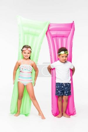 Kids in swimwear on swimming mattresses