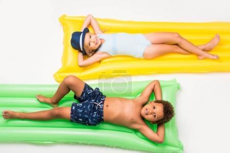 Photo pour Adorables enfants multiethniques en maillots de bain couchés sur des matelas isolés sur du blanc - image libre de droit
