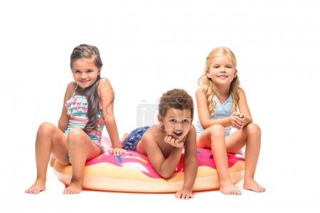Photo pour Adorables enfants multiethniques s'amusant sur le tube de natation isolé sur blanc - image libre de droit