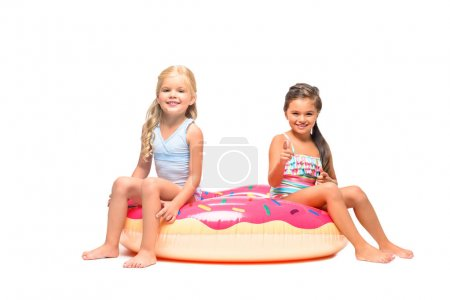 kids sitting on swim tube