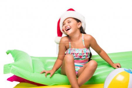 Child in santa hat on swimming mattresses