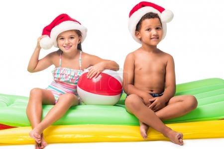 Photo pour Adorables enfants multiethniques dans des chapeaux de Père Noël assis sur des matelas de natation isolés sur blanc - image libre de droit