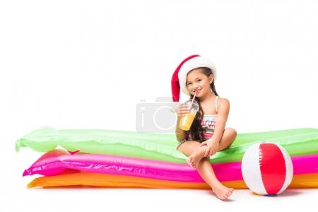 kid in santa hat with orange juice