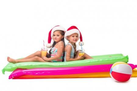 Photo pour Mignonnes petites filles en chapeaux Santa boire du jus d'orange tout en étant assis sur des matelas de natation - image libre de droit
