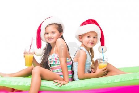 Photo pour Adorables petites filles en chapeaux Santa boire du jus d'orange tout en étant assis sur des matelas de natation - image libre de droit
